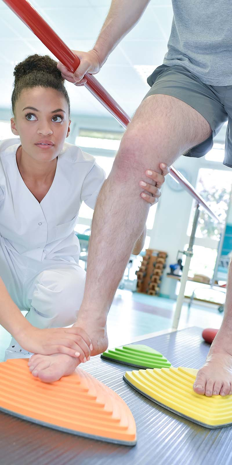 Female nurse having her client step on some foam pads as part of a rehabilitation method.