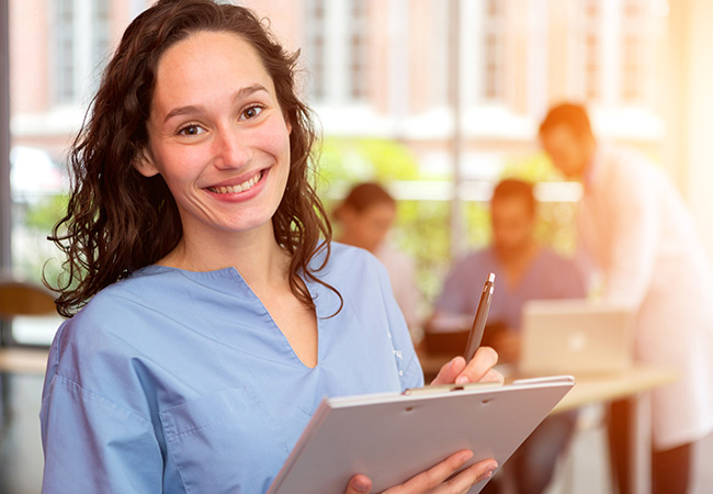 Image of a nurse smiling at the camera while holding a pen and notepad.